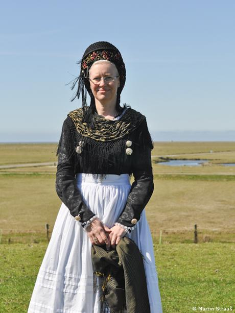 Karen Tiemann wearing traditional costume of a black frilly top, long white skirt and a black bonnet