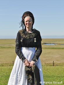 Mulher com vestido e cobertura na cabeça pretos e avental branco
