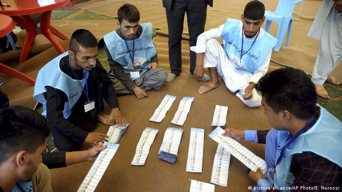 Afghan election workers count ballots at a polling station in Kabul