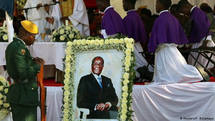 Soldiers stand beside a picture of former Zimbabwean President Robert Mugabe during a church service before his burial