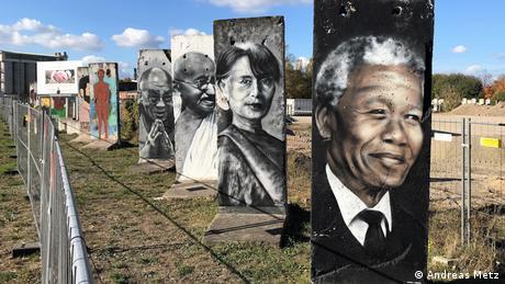 Rostos de personalidades mundiais pintados em pedaços remanescentes do Muro de Berlim
