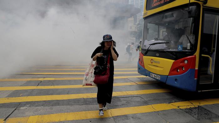 A woman moves away from a thick cloud of tear gas and smoke
