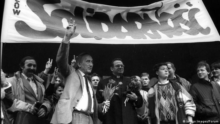Tadeusz Mazowiecki (en el centro, con saco, camisa y corbata) frente a una pancarta de Solidaridad en un evento en abril de 1989.
