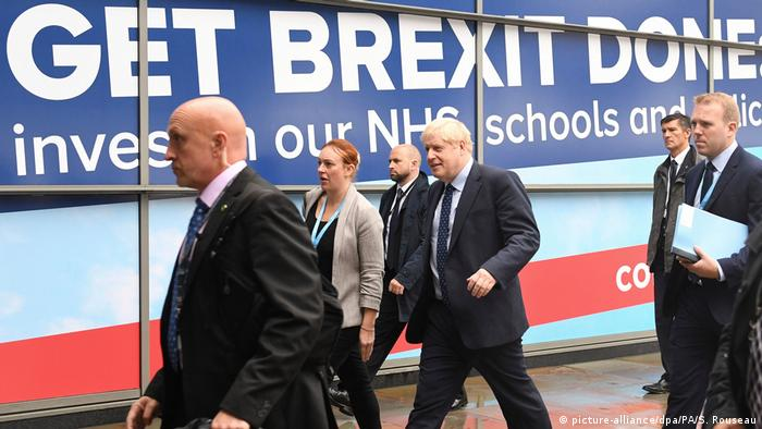 Boris Johnson standing in front of sign that reads 'Get Brexit Done'