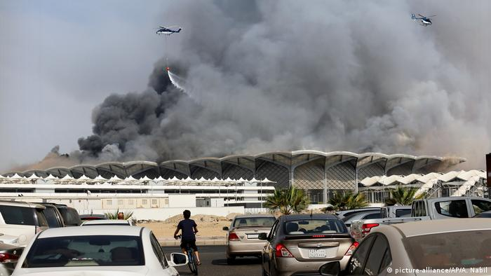 A firefighting helicopter sprays water on a fire at a train station in Jeddah, Saudi Arabia