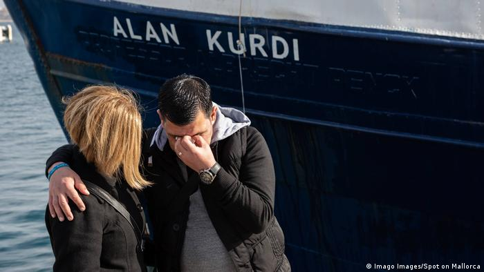 Abdullah Kurdi cries with his sister Tima Kurdi in front of a rescue ship named after his dead son Alan Kurdi