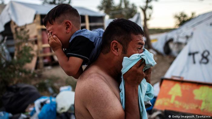 A man and boy crying after a clashes and a fire at the Moria refugee camp