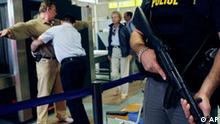An armed Swiss police officer, right, stands guard next to a Passenger Security employee of the Geneva airport, center, who frisks a passenger at a security checkpoint at the Swiss International Airlines boarding gate of a flight to New York, at Geneva International Airport, in Geneva, Switzerland, Tuesday, August 15, 2006. The prohibition to transport liquids in the hand luggage and the body search of the passengers was required by the US government for all the planes going to the US. (KEYSTONE/Salvatore Di Nolfi)