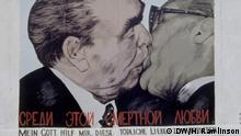 Die Berliner Mauer 30 Jahre danach - The Berlin Wall 30 Years Later. This painting depicts a photograph of Leonid Brezhnev and Erich Honecker in a fraternal embrace captured during the 30th anniversary celebration of the foundation of the GDR. Foto: Hallie Rawlinson / DW am 21.9.2019