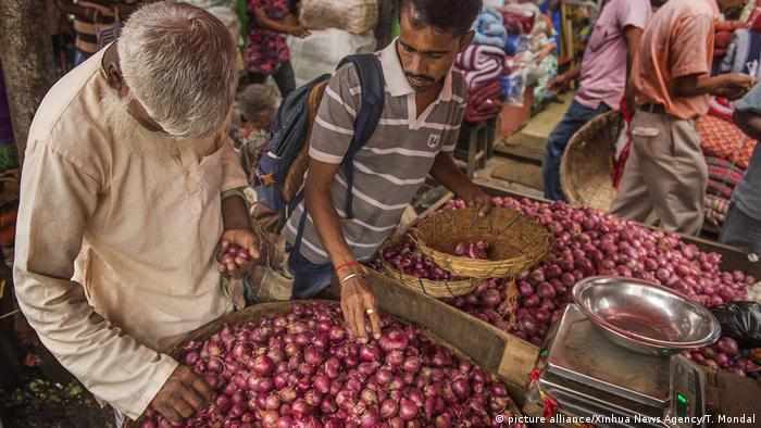 People buy onions at an onion wholesale market in Kolkata
