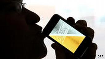 Als Silhouette ist ein Mann mit einem neuen iPhone des Herstellers Apple zu erkennen. Auf dem Display stellt das App-Programm iPint ein Glas mit Bier dar (Foto: dpa)