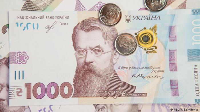 Купюра номіналом у 1000 гривень та кількагриневі монети