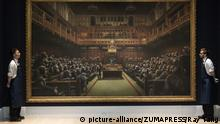 September 27, 2019, London, London, United Kingdom: Sotheby's staff view a painting titled Devolved Parliament, 2009, by artist Banksy. The painting depicts MP's in the houses of Parliament with an estimate of £1.5-2 million. The work is part of the Sotheby's contemporary art auction. (Credit Image: © Ray Tang/ZUMA Wire |