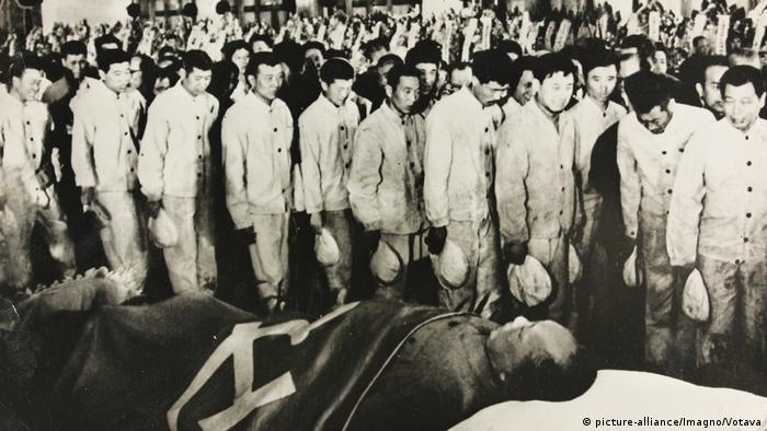 People walk past Mao Zedong at his funeral