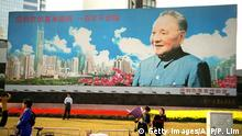 The huge billboard of the late patriarch Deng Xiaoping, the architect of China's economic reform program, takes center stage at a busy intersection in Shenzhen, southern China's special economic zone (SEZ) 14 February a few days before the first anniversary of Deng's death. Small, unofficial ceremonies at the billboard, which commemorates Deng's famous 1992 tour of southern China's economic boom town, are expected on 19 February, the anniversary of his death. AFP PHOTO/Peter LIM (Photo credit should read PETER LIM/AFP/Getty Images)
