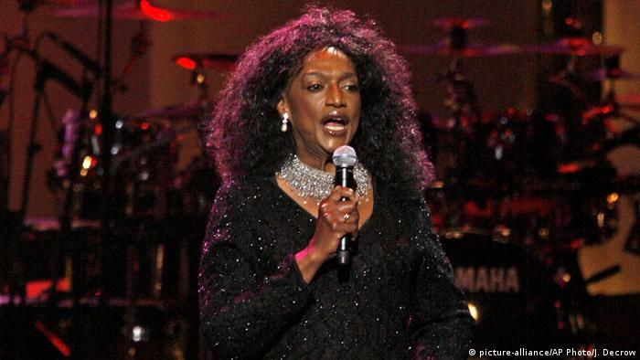 Jessye Norman in a black sequined dress and lavish diamond necklace sings into a microphone