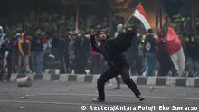 A protester throws a stone during clashes with police at a students' protest in Jakarta, September 25, 2019 in this photo taken by Antara Foto. Antara Foto/Indrianto Eko Suwarso/ via REUTERS ATTENTION EDITORS - THIS IMAGE WAS PROVIDED BY A THIRD PARTY. MANDATORY CREDIT. INDONESIA OUT.