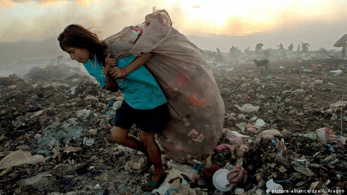 A girl carrying a sack of trash on a sprawling dump site