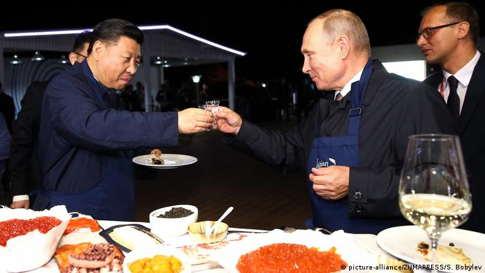 Russian President Vladimir Putin toasts Chinese President Xi Jinping with Russian vodka during the Eastern Economic Forum in September 2018 in Vladivostok, Russia