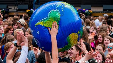 Symbolbild Weltkugel Junge Leute halten große aufblasbare Weltkugel hoch