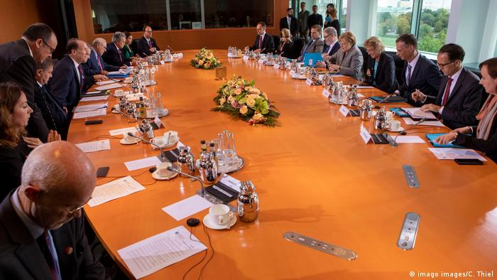 Angela Merkel around a board table in Berlin with top officials from the WTO, IMF, OECD, World Bank and ILO.