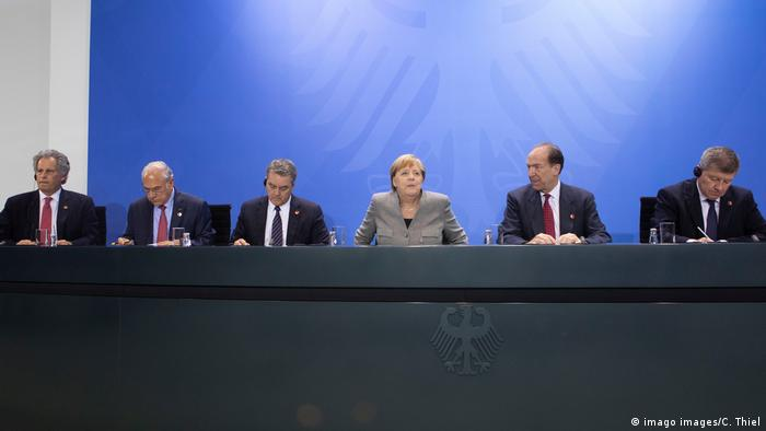 German Chancellor Merkel siuts with international finance ministers at a WTO meeting in Berlin on Tuesday