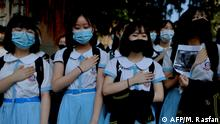 Schoolmates of form five student Tsang Chi-kin, 18, who was shot in the chest by police during violent pro-democracy protests that coincided with China's October 1 National Day, place their hands on their chests during a protest at a school in Hong Kong on October 2, 2019. - Hundreds of Hong Kongers staged a sit-in on October 2 outside the school of a protester who was shot by police as authorities said the wounded 18-year-old was now in a stable condition. (Photo by Mohd RASFAN / AFP)