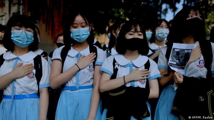 Schoolmates of Tsang Chi-Kin place their hands on their chests during a protest at a school