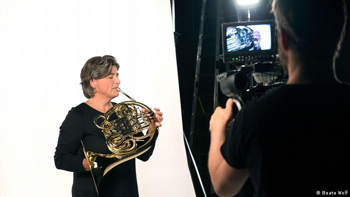 Split screen with a female horn player and a camera man with the instrument on his display | Dreh (Beate Wolf)