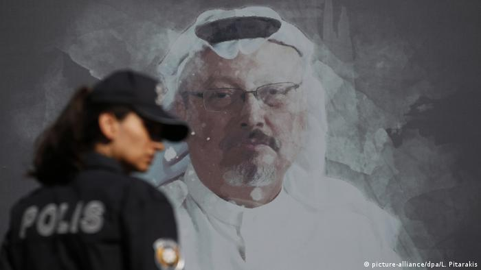 Polizistin vor dem Wandbild von Jamal Khashoggi