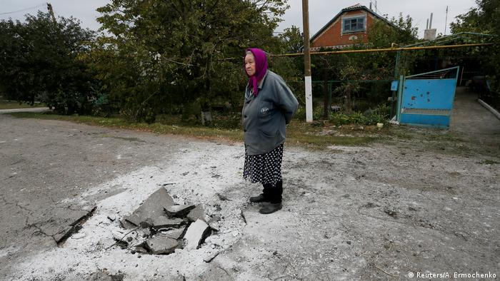 A woman stands on a bombed street in Eastern Ukraine