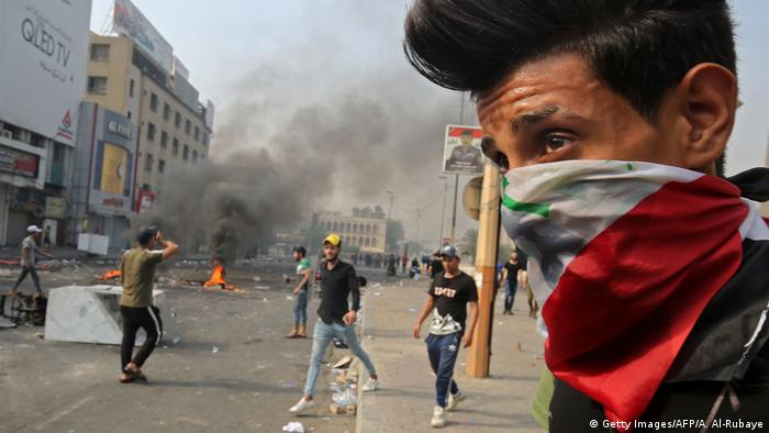 Protester wearing Iraqi flag, smoke and other protesters