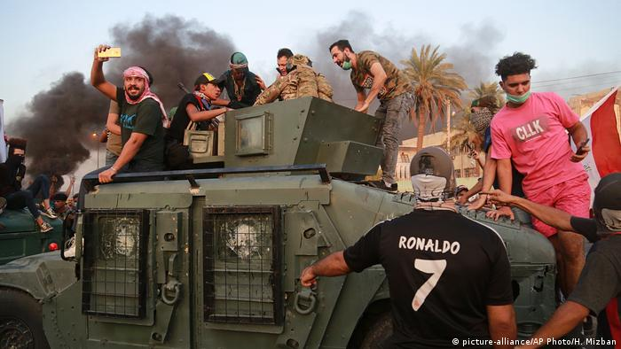 Iraq protesters face off with soldiers as thery try to take over a armored vehicle (picture-alliance/AP Photo/H. Mizban)