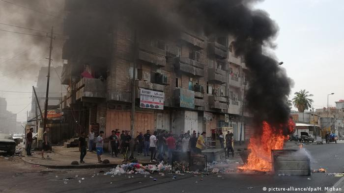Protest in Bagdad show smoke rising from a dumpster that is on fire as part of anti-government protests (picture-alliance/dpa/H. Mizban)