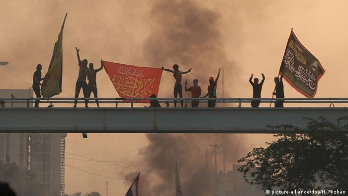 People stand on a bridge and wave flags at a protest in Baghdad (picture-alliance/dpa/H. Mizban)