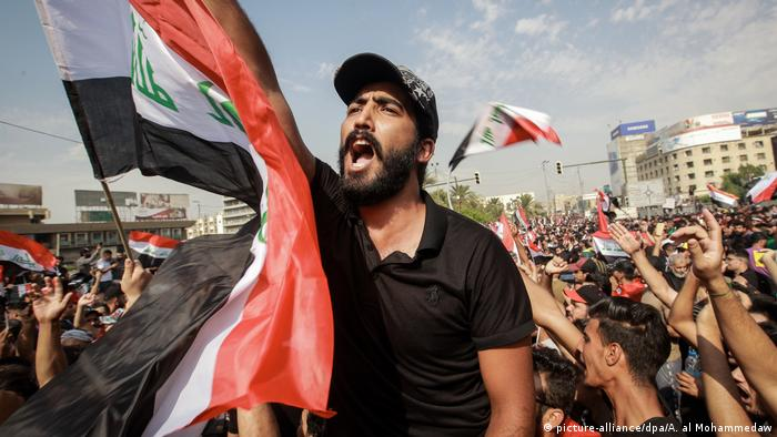 A man waves an Iraqi flag at anti-government protests in downtown Baghdad (picture-alliance/dpa/A. al Mohammedaw)