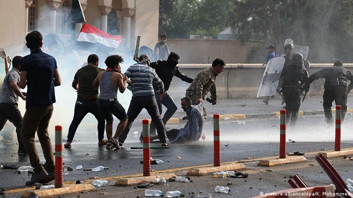 Security forces run after protesters in Baghdad while unleashing tear gas (picture-alliance/dpa/K. Mohammed)
