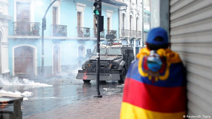 A man wrapped in an Ecuadorian flag huddles against the wall as an armored car rolls down the street (Reuters/D. Tapia)