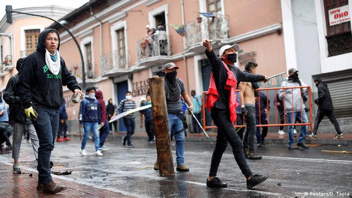 Protesters walk down the street in Quito