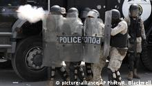 Police fire tear gas as they try to block anti-government protestors from reaching United Nations headquarters, in Port-au-Prince, Haiti, Friday, Oct. 4, 2019. Thousands of protesters marched through the Haitian capital to the U.N. headquarters Friday in one of the largest demonstrations in a weekslong push to oust the embattled President Jovenel Moise. (AP Photo/Rebecca Blackwell)  