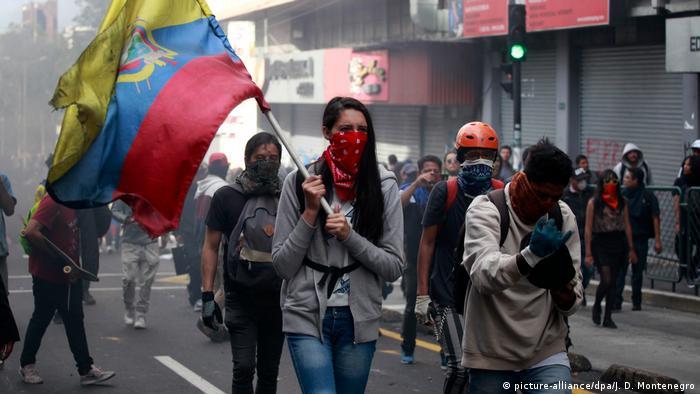 A protester in Ecuador holds an Ecuadorian flag and wears a bandanna covering her face