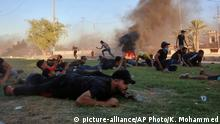 Anti-government protesters take cover while Iraq security forces fire during a demonstration in Baghdad, Iraq, Friday, Oct. 4, 2019. Security forces opened fire directly at hundreds of anti-government demonstrators in central Baghdad, killing several protesters and injuring dozens, hours after Iraq's top Shiite cleric warned both sides to end four days of violence before it's too late. (AP Photo/Khalid Mohammed)  