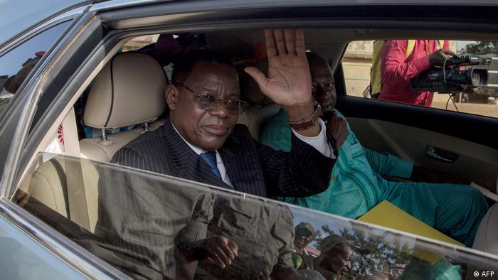 Cameroonian opposition leader Maurice Kamto waves as he sits in the back of a car (AFP)