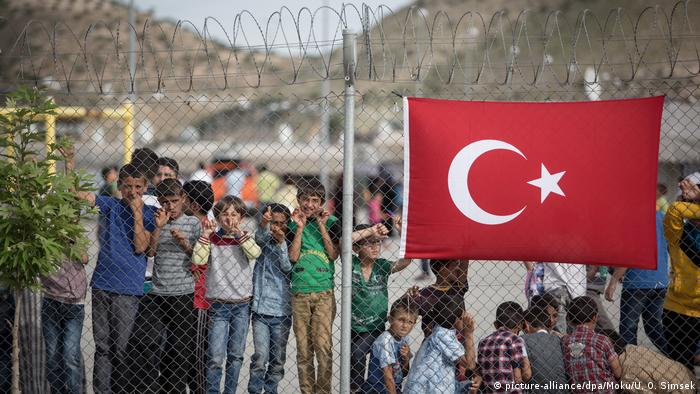 Refugee children in Gaziantep behind a fence with a Turkish flag on it