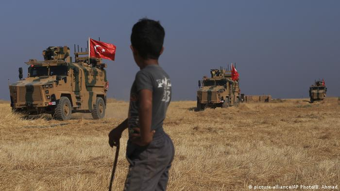 A child watches a Turkish armored vehicle patrol in Syria
