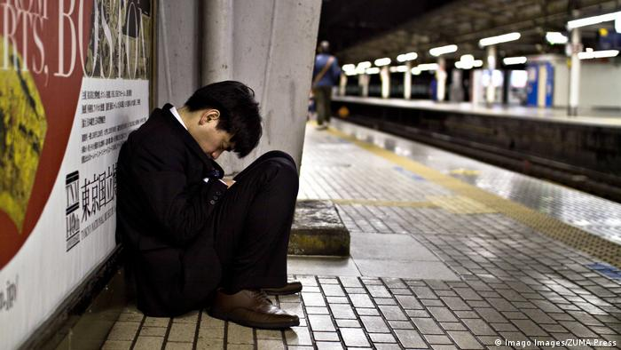 A Japanese businessman snoozes after missing the train late at night in Tokyo