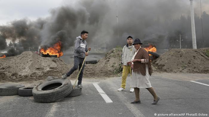 Homens constroem barricada com pneus, com fogo e fumaça ao fundo