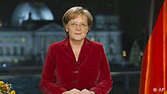 German Chancellor Angela Merkel poses after the recording of her New Year's Eve speech with German flag by her side