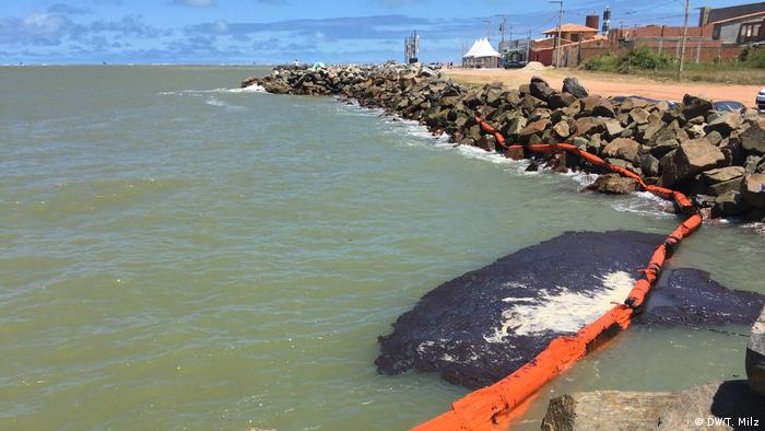 A red containment boom holds back an oil spill in Atalaia, Aracaju (DW/T. Milz)