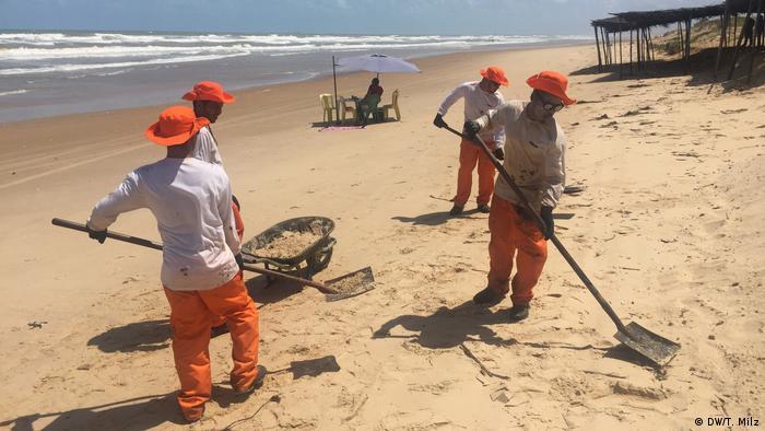 Funcionários trabalham na limpeza de pedaços de óleo na praia de Pirambu, no litoral norte do Sergipe